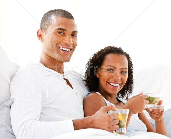 Happy couple drinking a cup of tea lying on their bed Stock photo © wavebreak_media