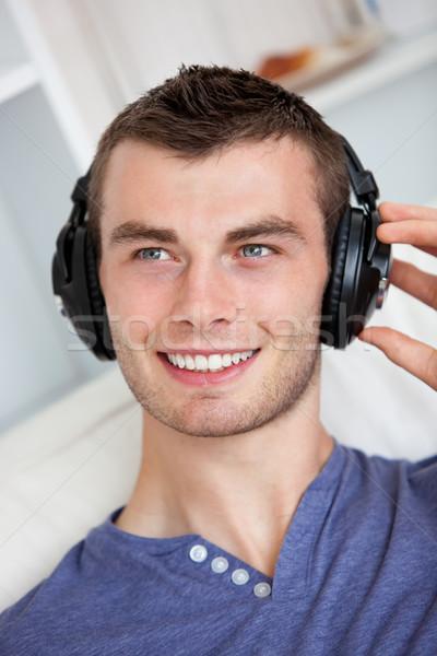 Przystojny młody człowiek słuchanie muzyki słuchawki domu uśmiech Zdjęcia stock © wavebreak_media