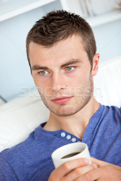 Charming caucasian man holding a cup of coffee in the living-room at home Stock photo © wavebreak_media