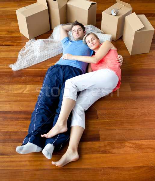Couple lying on floor by close boxes in new home smiling Stock photo © wavebreak_media