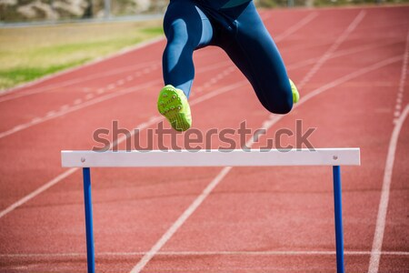 Serious male athlete jumping above hedge during a race in a stadium Stock photo © wavebreak_media