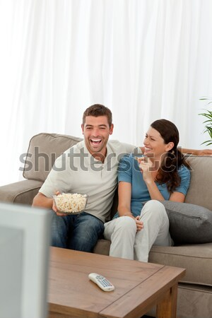 Scared couple hiding their faces while watching a horror movie in the living room Stock photo © wavebreak_media