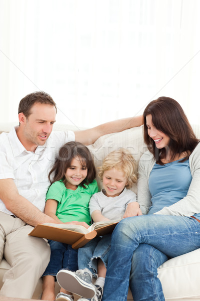 Cheerful family looking at a photo album together on the sofa Stock photo © wavebreak_media