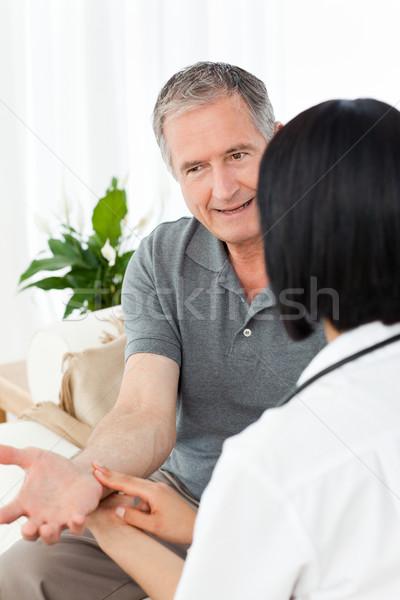 Nurse taking the pulse of  her patient Stock photo © wavebreak_media