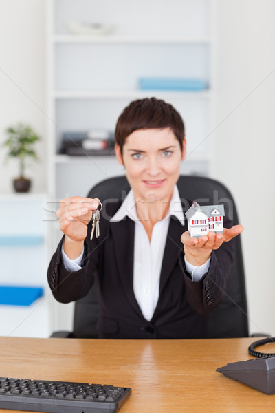 Portrait of a businesswoman showing a miniature house and a key in her office Stock photo © wavebreak_media