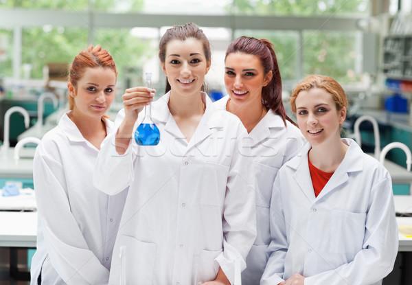 Labor partnerek pózol flaska néz kamera Stock fotó © wavebreak_media