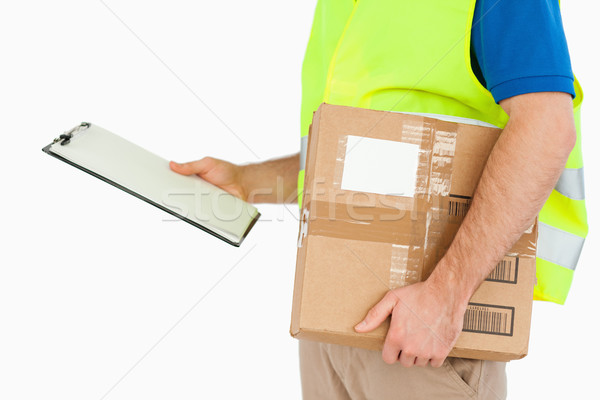 Side view of young delivery man with delivery note and parcel against a white background Stock photo © wavebreak_media