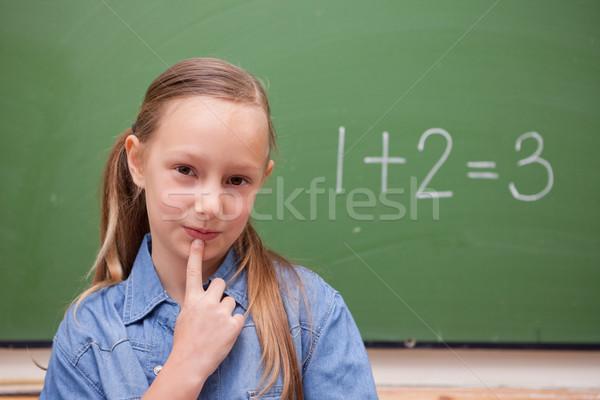 Smiling schoolgirl thinking in front of a blackboard Stock photo © wavebreak_media