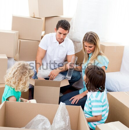Family unpacking cardboard box in the living room together Stock photo © wavebreak_media