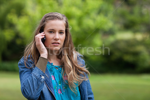 Jonge ernstig vrouw praten telefoon permanente Stockfoto © wavebreak_media