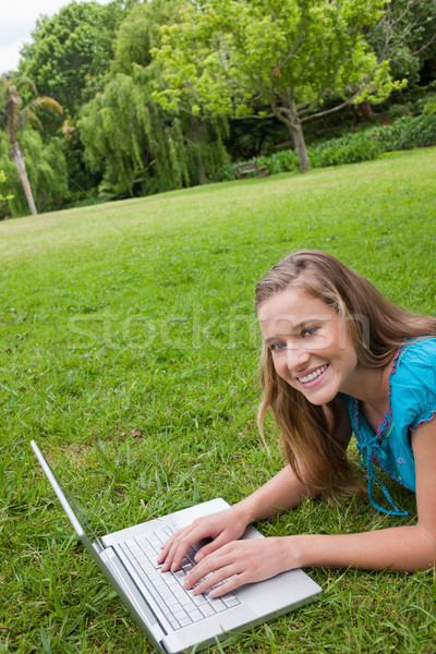 Smiling young girl lying on the grass in a public garden while working on her laptop Stock photo © wavebreak_media