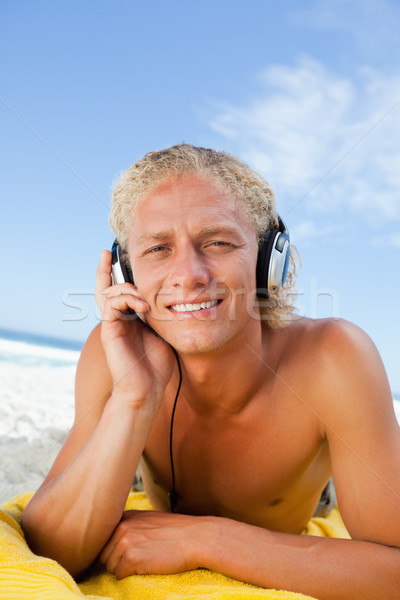 Young blonde man attentively listening to music with his headset Stock photo © wavebreak_media