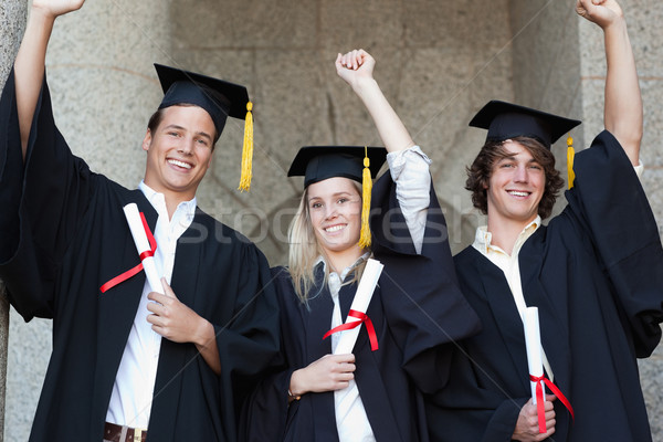 Graduates holding their diploma while raising arm with university in backgroung Stock photo © wavebreak_media