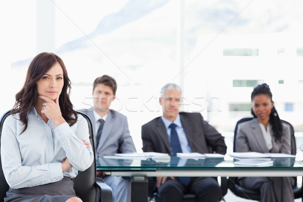Young businesswoman almost smiling with her hand on her chin in a bright meeting room Stock photo © wavebreak_media