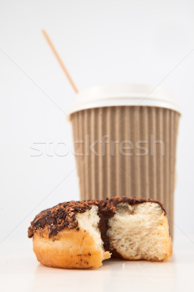 An half eaten doughnut and a cup of coffee placed together against a white background Stock photo © wavebreak_media