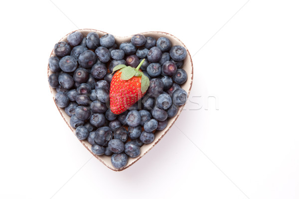 Blueberries and one Strawberry  in  a heart shaped bowl against a white background Stock photo © wavebreak_media