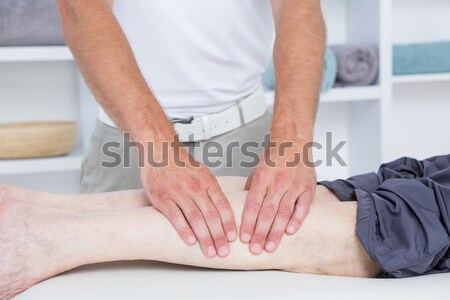 Serious physiotherapist stretching the leg of a patient in a room Stock photo © wavebreak_media