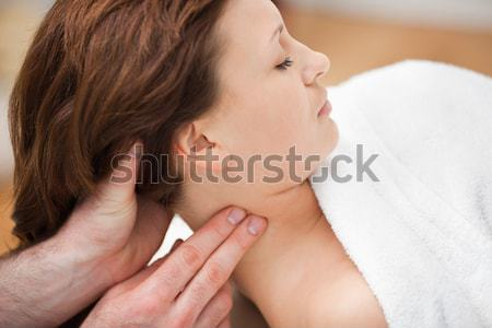 Therapist massaging the neck of woman while holding her head in a room Stock photo © wavebreak_media