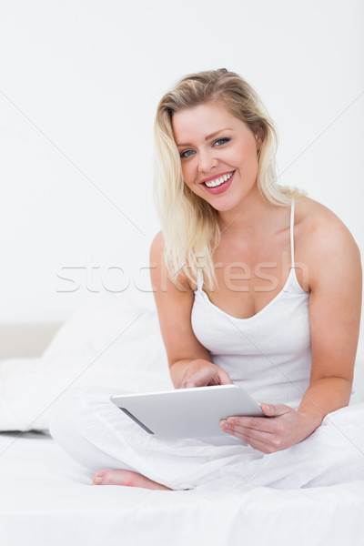 Blonde smiling while holding an ebook on her bed Stock photo © wavebreak_media