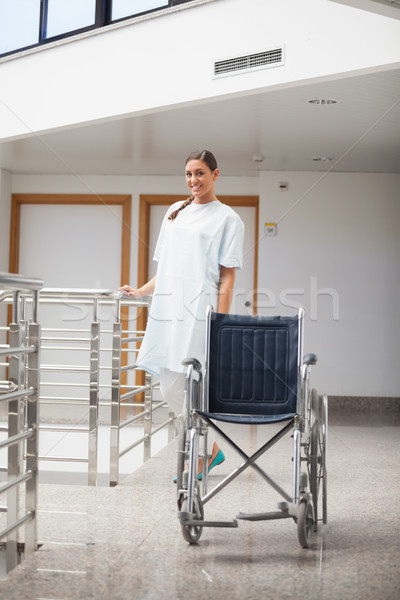 Stock photo: Smiling patient standing next to a wheelchair in hospital hallway