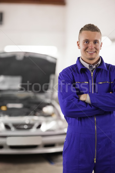 Smiling mechanicarms crossed next to a car in a garage Stock photo © wavebreak_media
