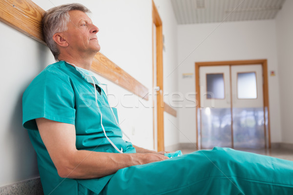 Tired surgeon is sitting on the floor in hospital corridor wearing green scrubs Stock photo © wavebreak_media