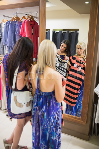 Women standing at the mirror holding up clothes in shopping mall Stock photo © wavebreak_media