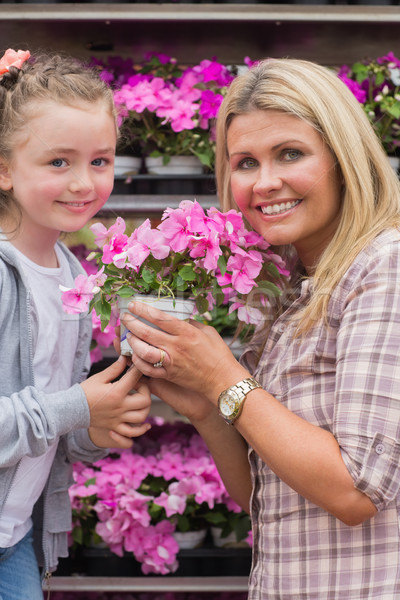 Stock photo: Mother and child holding a flower in garden centre