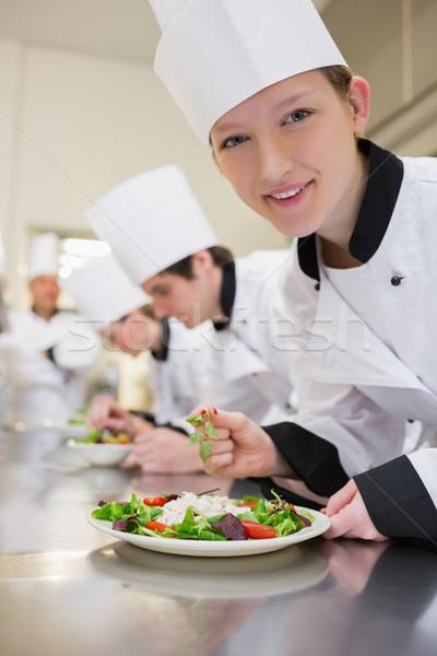 Smiling chef preparing salad in culinary class in kitchen Stock photo © wavebreak_media