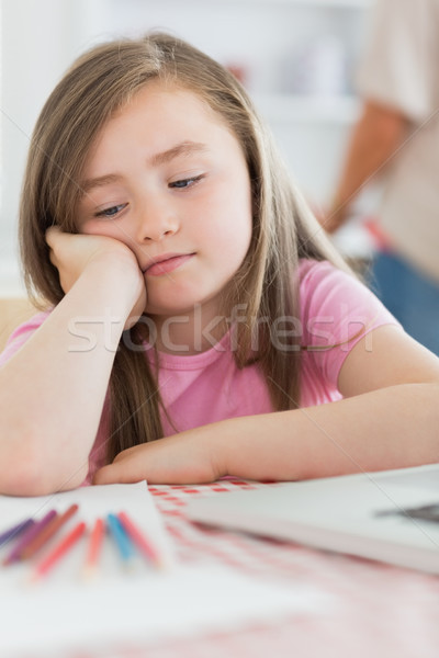 Stock photo: Girl sitting while looking bored with paper and colouring pencils in kitchen