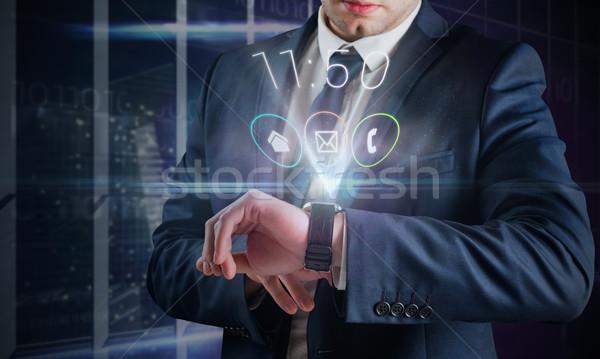 Composite image of businessman using hologram watch Stock photo © wavebreak_media