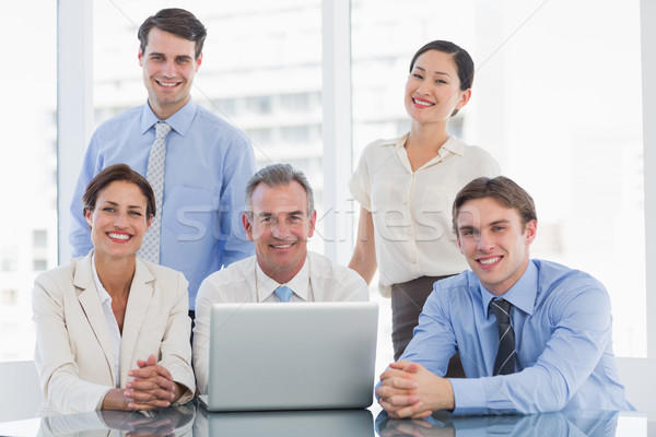 Negocios colegas portátil escritorio grupo sonriendo Foto stock © wavebreak_media