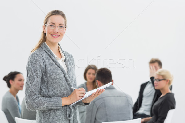 Portrait of therapist with group therapy in session in backgroun Stock photo © wavebreak_media