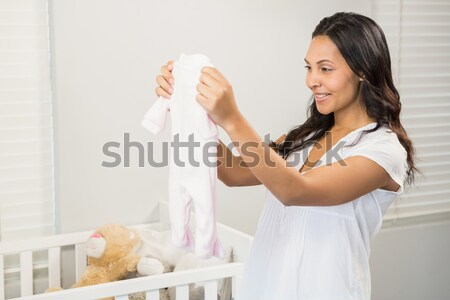 Happy woman flexing muscles while drinking water in kitchen Stock photo © wavebreak_media