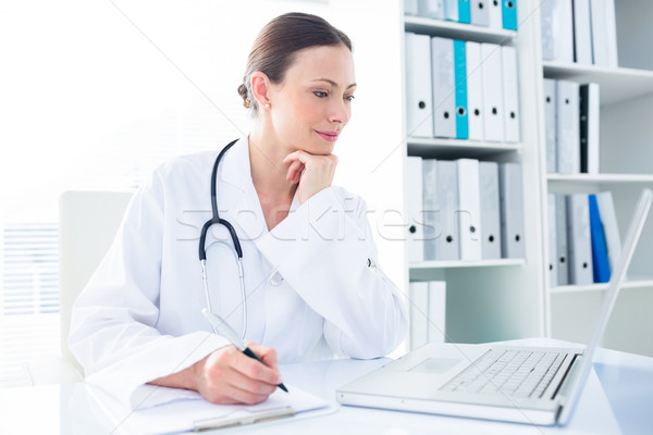 Doctor writing while using laptop Stock photo © wavebreak_media