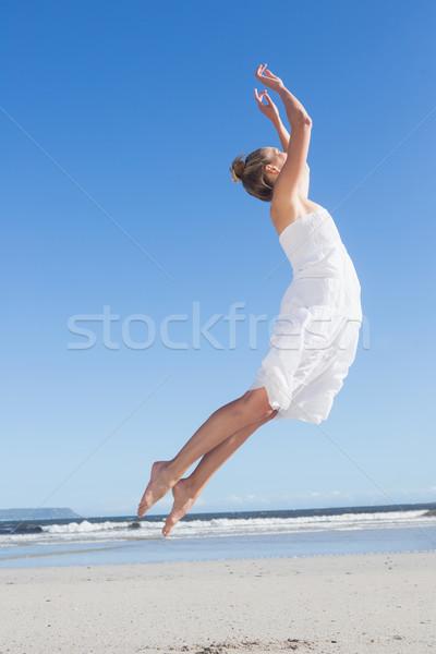 Pretty blonde in white dress leaping on the beach  Stock photo © wavebreak_media