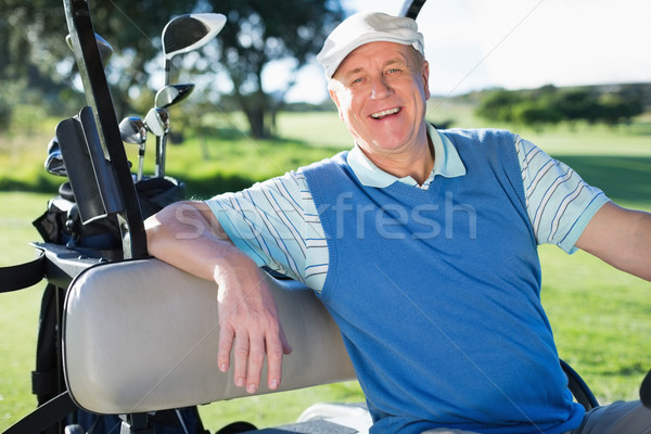 Happy golfer driving his golf buggy smiling at camera Stock photo © wavebreak_media