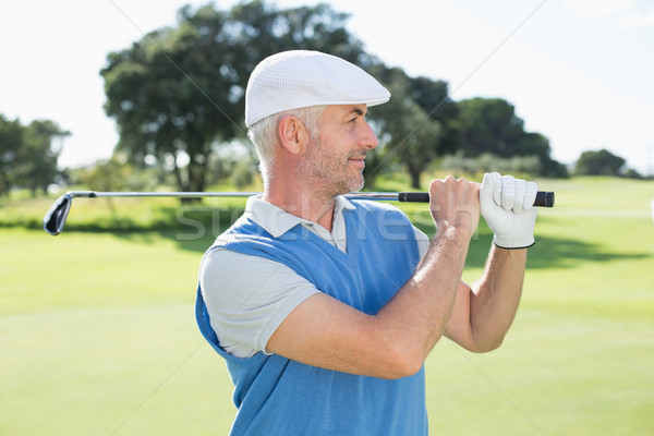 Golfer standing and swinging his club Stock photo © wavebreak_media