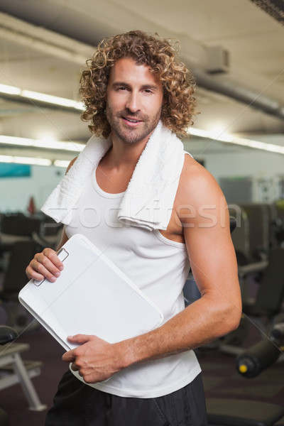 Smiling handsome trainer with clipboard in gym Stock photo © wavebreak_media