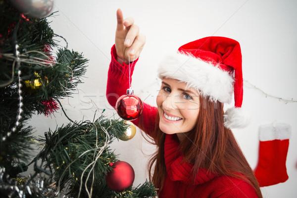 Festive redhead hanging bauble on tree Stock photo © wavebreak_media