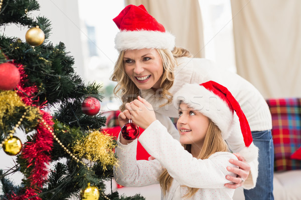 Festive mother and daughter decorating christmas tree Stock photo © wavebreak_media