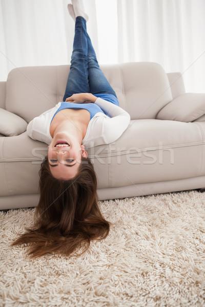 Bastante morena de cabeça para baixo sofá casa sala de estar Foto stock © wavebreak_media