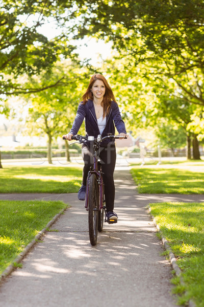 Pretty redhead cycling a bike Stock photo © wavebreak_media