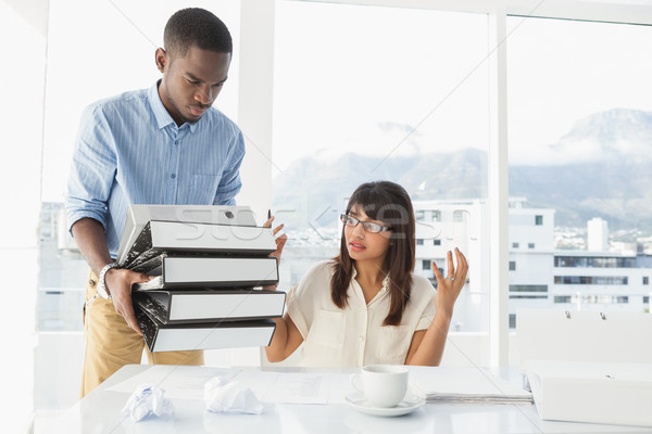 Man giving pile of files to his exasperated colleague Stock photo © wavebreak_media