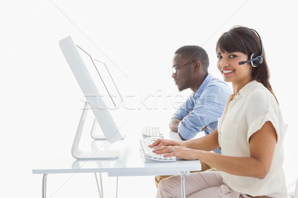 Smiling teamwork using computer and headset Stock photo © wavebreak_media