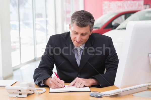 Businessman writing on clipboard at his desk Stock photo © wavebreak_media
