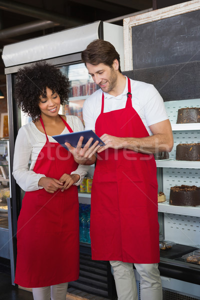 Smiling colleagues in red apron using tablet together Stock photo © wavebreak_media