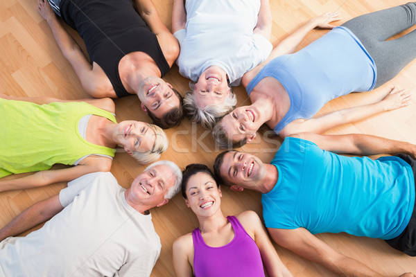 Happy people lying on hardwood floor at gym Stock photo © wavebreak_media