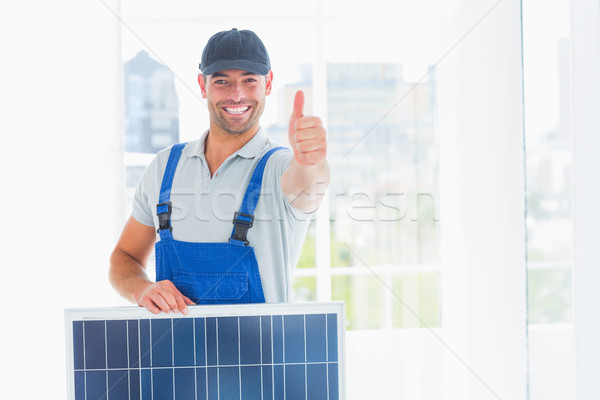 Workman with solar panel gesturing thumbs up in bright office Stock photo © wavebreak_media