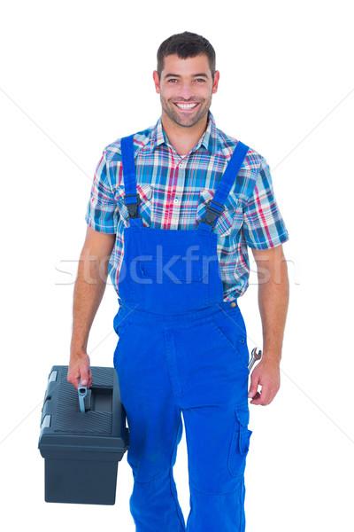 Happy handyman in coveralls carrying toolbox Stock photo © wavebreak_media
